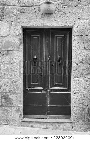 Building with traditional maltese door in historical part of Valletta. Entrance to an abandoned house on the island of Malta. Black and white picture