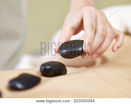 close-up of hand of a masseur placing stone on back of customer to perform hot stone massage.