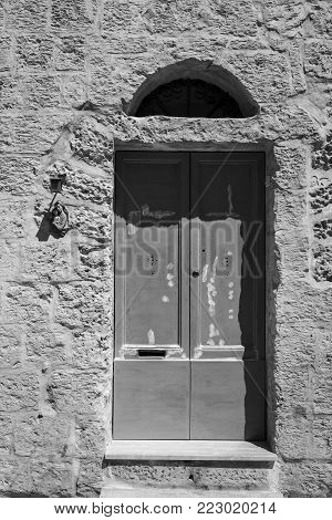 Outdoor relief of Virgin Saint Mary, Madonna with Child, near the door.  Entrance to a old house on the island of Malta. Black and white picture