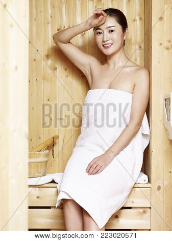 beautiful young asian woman wrapped in white towel sitting in sauna looking at camera smiling.