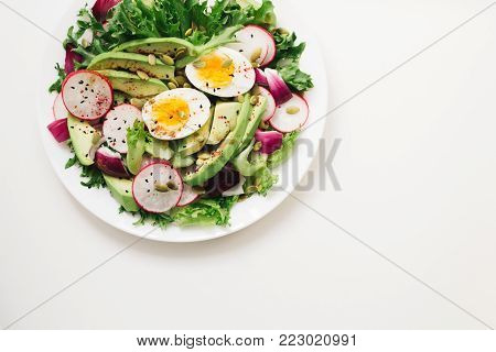 Homemade Fresh spring salad with rucola, radish with red onion and avocado with eggs in white bowl on chalkboard background with free text space. healthy winter vegetarian food. Top view