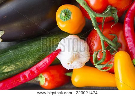 Preparing Healthy Food, Vegeterian, Vegan Concept. A close up of fresh whole vegetables: zuccini, eggplant, tomatoes, chilli peppers and garlic, top view
