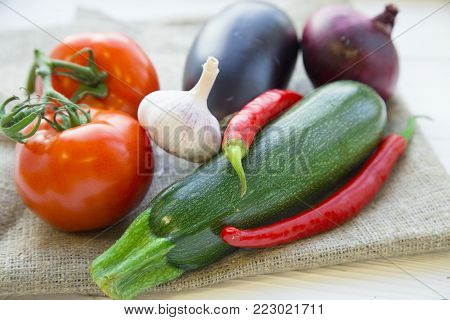 Healthy Food, Vegeterian, Vegan Concept. A set of fresh whole vegetables: zuccini, eggplant, tomatoes, chilli peppers, red onion and garlic on a linen cloth