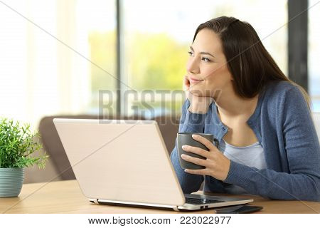 Distracted woman dreaming beside a laptop on a table at home