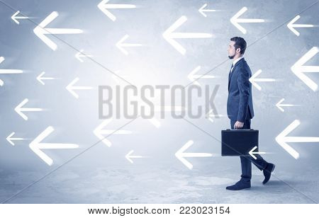 Businessman walking with arrows on the background and briefcase on his hand