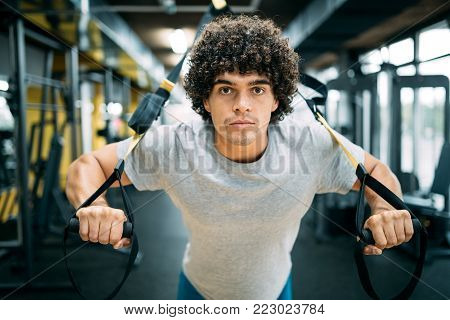 Photo of handsome young sporty man. Man training with TRX Suspension at fitness club
