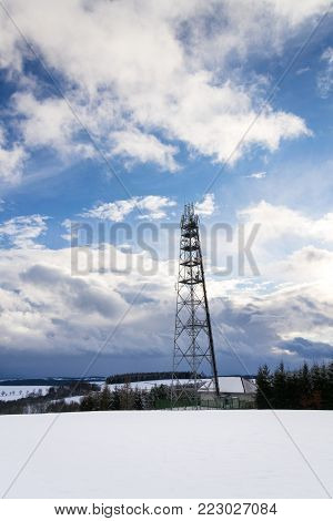 Snowy Winter Country With Transmitters And Aerials On Telecommunication Tower