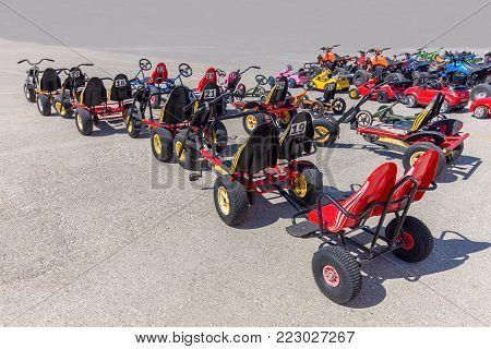 Many go-karts for children standing on asphalt terrain