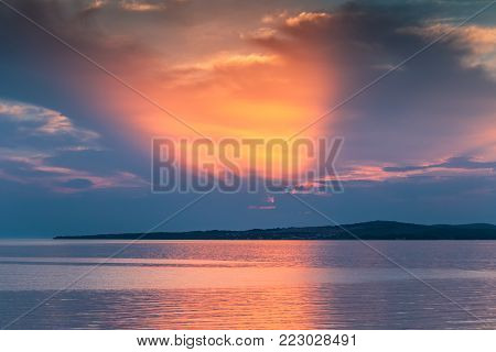 Sunset at sea with the rays of the sun through the clouds in beautiful colors. Island Vir on Adriatic Sea, Croatia, Europe.
