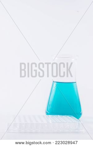 research, science and clinic background. 96 well micro plate and  laboratory beakers with colorful liquids and reagents.