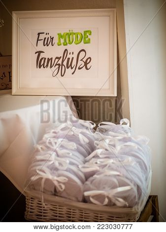 Rattan basket with white flip-flops of different sizes for guests, with a writing DANCING SHOES. KICK OFF YOUR HEELS