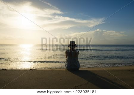 Woman sitting on a beach and watching the sun set