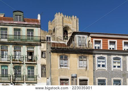Detail of the facade of traditional buildings with the bell tower of the Lisbon Cathedral on the background in Lisbon, Portugal; Concept for visit Lisbon.