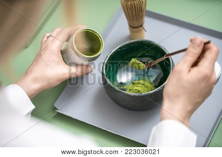 Blonde girl prepares a chinese matcha green tea on the green metal table indoors. She puts tea powder into the emerald bowl. On the table there is a wooden tea whisk. Closeup. Horizontal.