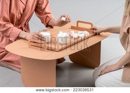 Textured glasses with milk and marshmallows on the orange metal tray on the table on a gray background in the studio. Couple of girls sitting near the table. One woman holds the  marshmallow.