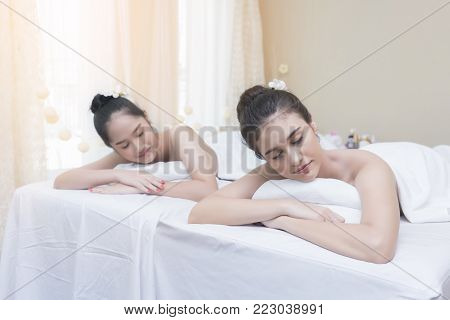 Beautiful Asian young women lying on massage table waiting for spa treatment