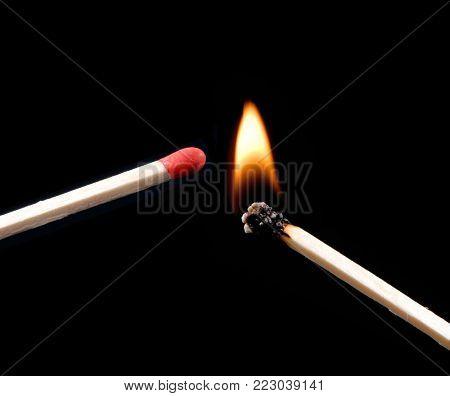 lighting flaming matchstick on black background.