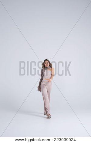 Full-length shot of smiling girl in stylish clothes walking towards camera