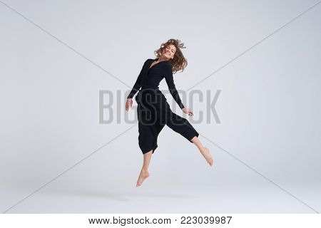 Full-length shot of cheerful young woman hovering in the air