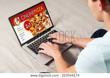 Man ordering pizza by internet with a laptop computer, sitting at home.