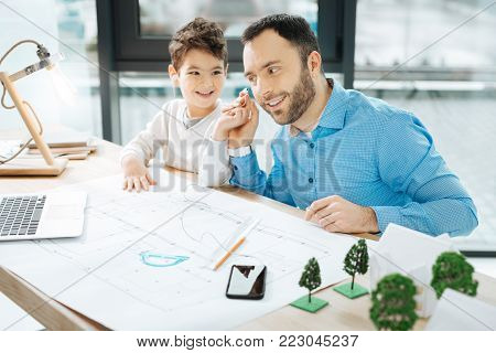 Nice song. Upbeat young landscape designer sitting at the table in the office together with his son and listening to the music with him