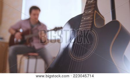 Young attractive musician composes music on the guitar and play, other musical instrument in the foreground, blurred, sitting full face