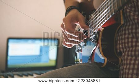 Young male musician composes and records soundtrack playing the guitar, using computer, headphones and keyboard, focus on equipment