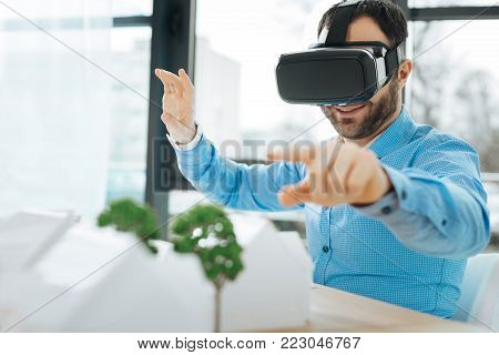 Effective approach. The focus being on an upbeat bristled young architect sitting in the office and pointing at the models of houses and trees sitting at the table while wearing a VR headset