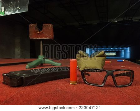 Photo of shooting gallery with glasses, pistol, sleeve, clip on brown table