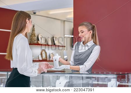 Attractive blonde female worker in a white blouse and grey uniform with white gloves on her hands showing a necklace with a stone in it to a long-haired female client wearing a chic white blouse in a modern jewelry store.