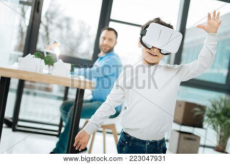 New toy. Upbeat little boy testing a new VR headset during a visit to his fathers office while the man working on a new project at the table