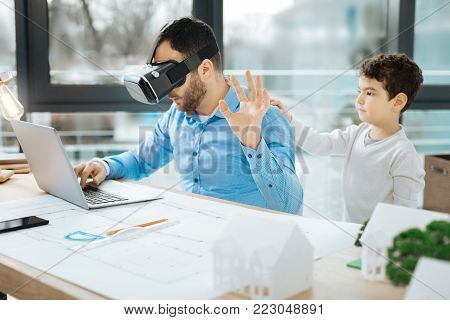 Wait a second. Bristled young architect in a VR headset working on a project and raising his hand as if asking his son touching his back not to distract him