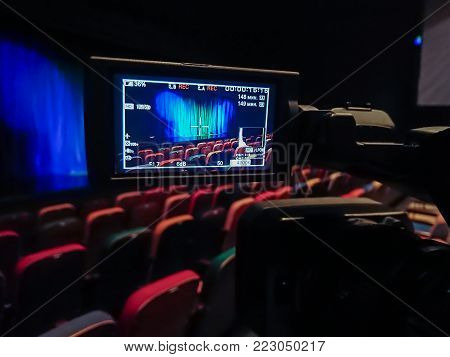 The LCD display on the camcorder. Videography in the theater. Blue-green curtain on the stage.