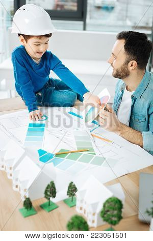 Crucial advice. Charming young architect sitting next to his little son and discussing the color choice with him while the boy pointing at color in the color chart
