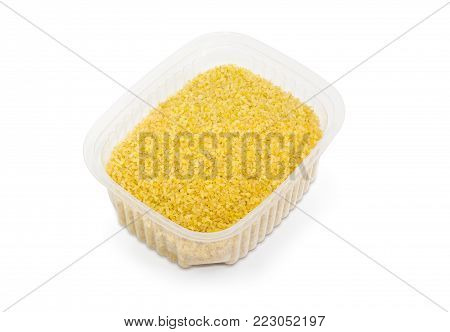 Uncooked bulgur in the small semi transparent plastic container on a white background