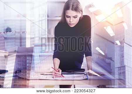 Portrait of attractive young businesswoman doing paperwork on abstract city background. Worker and engineering concept. Double exposure