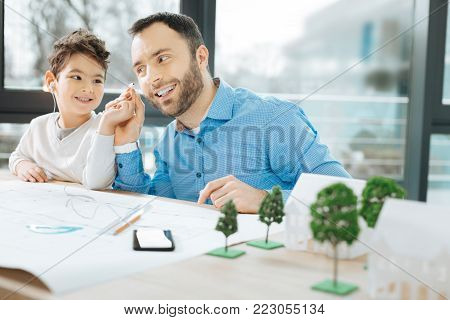 Generous child. Cheerful little boy sitting at the table next to his father and sharing earpieces with him while listening to the music together
