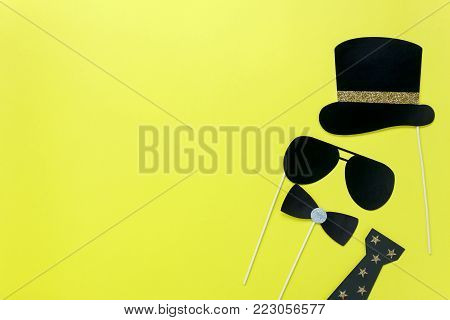 Table top view aerial image of beautiful colorful carnival mask or photo booth props background.Flat lay objects on modern rustic yellow wallpaper at office desk studio.space for creative mock up.