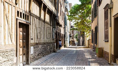 TROYES, FRANCE - JUNE 29, 2010: woman near old half-timbered houses on Rue Larivey in Troyes town. Troyes city is the capital of the Aube department in Champagne region of Northern France