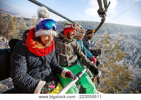 Happy young group of people in ski lift lifting on  ski terrain