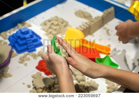 Kids playing plastic mold toys with sand on sandbox. Background blurry.