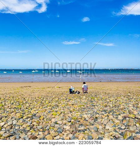PLOUBAZLANEC, FRANCE - JULY 3, 2010: vacationers on beach Plage de la Baie de Launay on bay Anse de Launay of English Channel in Paimpol region of Cotes-d'Armor department of Brittany in sunny summer