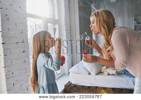 Who got bigger? Mother and daughter blowing soap bubbles while spending time at home
