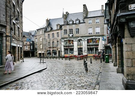DINAN, FRANCE - JULY 5, 2010: tourist on square Place des Merciers with wet pavement in Dinan city in rain. Dinan is a walled town and commune in the Cotes-d'Armor department of Brittany