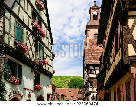 RIQUEWIHR, FRANCE - JULY 11, 2010: houses and vineyards of Riquewihr city. Riquewihr is commune in Alsace Wine Route region, the town belongs to the association The most beautiful villages of France