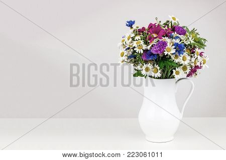 Old photo effect applied. Toned. Wildflowers in white ceramic jug with copy space. Wild flower bouquet on white table. Bunch of wild herbs and flowers in a white jug. Wild flowers in a vase.