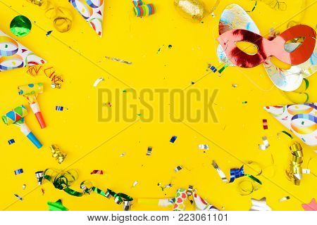 Bright colorful carnival or party frame of confetti and masks on yellow table. Flat lay style, birthday or party greeting card with copy space.