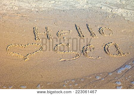 Words Hello Sea written in the sand on the beach..