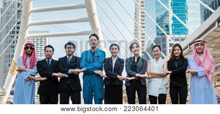 Hand coordination togetherness Multicultural business people group including Arabic, East Asian, Latin American standing in modern city. Concept of multi ethnic, multiracial business team.
