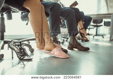 Home atmosphere in office. Young woman sitting on chair in rosy slippers on foreground. Home business concept.